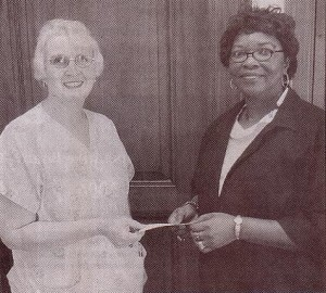 Eddie Mae Herron Center board member and treasurer Jessie Ann Johnson presents checks for $250 each to Lesa Lewallen, chairperson of the Relay for Life fundraiser