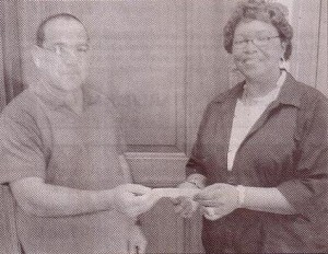 Eddie Mae Herron Center board member and treasurer Jessie Ann Johnson presents checks for $250 to Raul Blasini, local coordinator of the Men's Prostate Screening initiative.